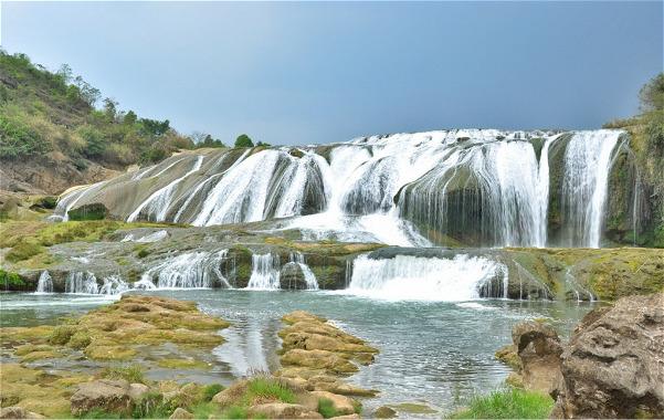 黄果树大瀑布不仅是中国最壮观美丽的瀑布,也是世界上唯一一个可以从上、下、前、后、左、右六个方位全面观赏的瀑布,世界少有的有水帘洞自然贯通且能从洞内外听、观、摸的瀑布,所以黄果树大瀑布也是能够看个真真切切、实实在在的美丽瀑布。其实黄果树不仅仅是一个大瀑布,黄果树景区分布着雄、奇、险、秀风格各异的大小18个瀑布,形成一个庞大的瀑布家族,被大世界吉尼斯总部评为世界上最大的瀑布群,当然,最出名也最壮观的就是高77.